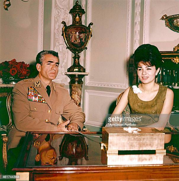 Wearing the military uniform the last Emperor of Persia Shah Mohammad Reza Pahlavi is portrayed in the study of the Royal Palace with his third wife...