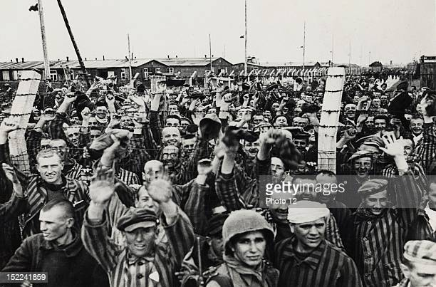 Wearing the striped uniform of the concentration camp happy prisoners at Dachau cheer troops of the 45th Div 7th US Army who liberated them on April...