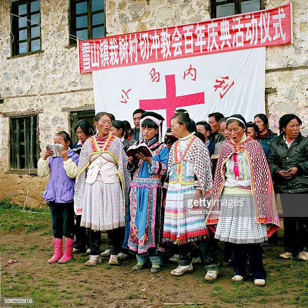 Wearing their traditional costumes Miao and Yi women sing hymns at Qie Chong village's 100 years anniversary of the Catholic church celebration...