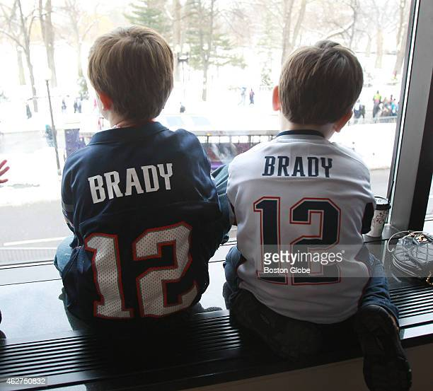 Wearing Tom Brady jerseys JP Martin left and TK Faria watch New England Patriots football team Super Bowl parade from a ballroom at the Four Seasons...