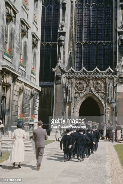 Wearing top hats and gowns, choristers from the Choir of King's College walk in line to the side entrance to King's College Chapel in Cambridge,...