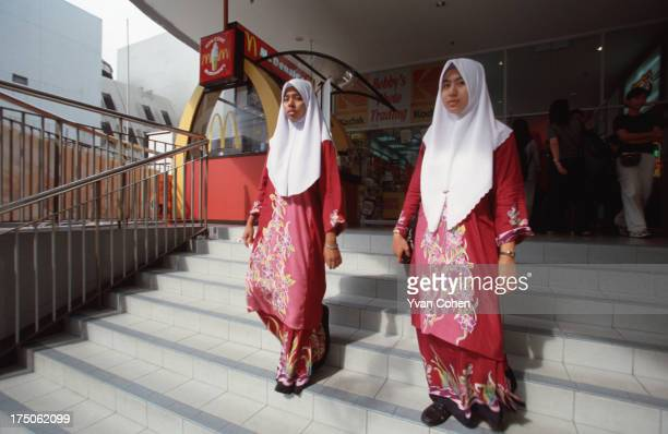 Wearing traditional hijab headscarves two muslim girls walk out of a shopping center in Penang Malaysia