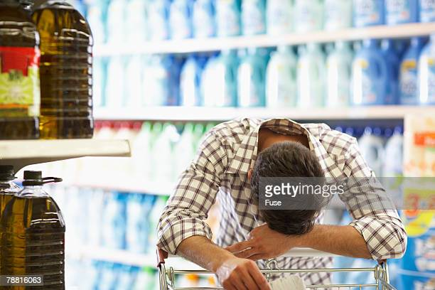 Weary Man Laying His Head On Shopping Cart High-Res Stock Photo ...