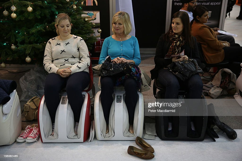 Weary shoppers enjoy an electronic massage at The Ideal Home Christmas Show on November 14, 2012 in London, England. Over 400 exhibitors are showcasing a range of gift ideas for Christmas at the Earls Court exhibition centre.