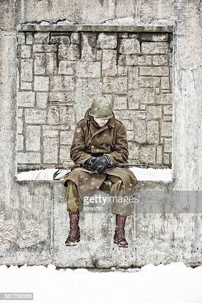 Weary WWII GI Sitting on a Wall In A Courtyard