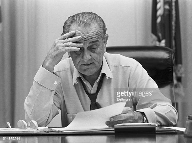 Weary-looking President Johnson looks at documents on his desk in the Cabinet Room of the White House. He is preparing an address on Vietnam.