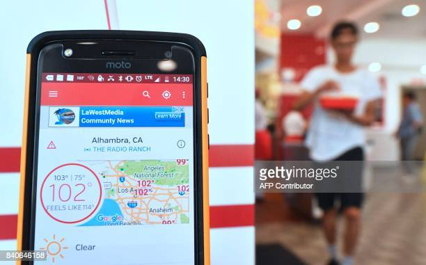 A weather app on a mobile phone shows triple digits inside a restaurant in Alhambra California amid an ongoing southern California heatwave on August...