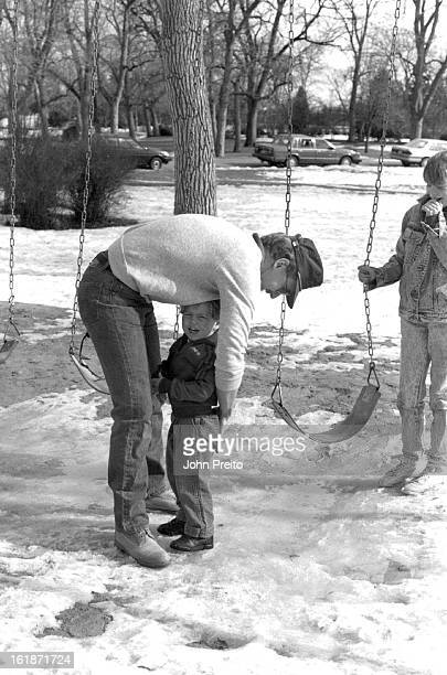 2/7/1988 FEB 8 1988 Weather Art'City Park Shot of Mr Mike Bush trying to comfort his son Matthew age 2 after he fell into the puddle of water below...