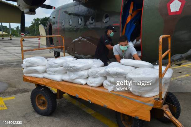 Weather modification officers load sacks of salt, to be used in cloud seeding operations to induce rainfall, onto an Indonesian Air Force CASA C-212...