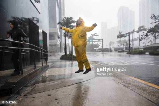Weather reporters jump and cling on to illustrate the force of the winds caused by Hurricane Irma as it arrives in Miami Fla on Sept 10 2017