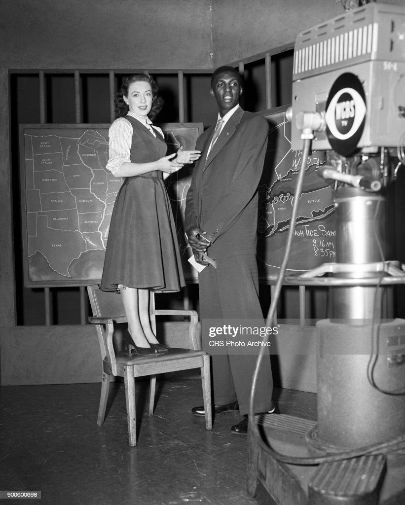 CBS weather segment, Rain or Shine featuring weather girl, Carol Reed and guest Walt Dukes of Seton Hall basketball team. New York, NY. Image dated April 29, 1953.