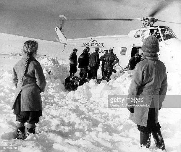8th January 1963, Stranded families, cut off by deep snow in the Lammermuir Hills, Scotland, greet a RAF, helicopter which was delivering supplies to...