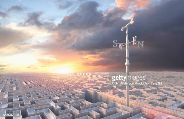 Weather vane above distant maze at sunset