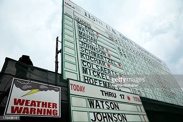 Weather warning sign is seen on a leaderboard on the 18th hole during Round One of the 113th U.S. Open at Merion Golf Club on June 13, 2013 in...