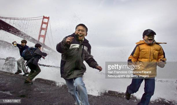 WEATHER_0148_fljpg Ryan Young center and his scout mate Jason Martin dodge the high surf at Fort Point under the Golden Gate Bridge during a Boy...