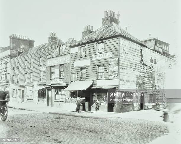 Weatherboard houses and shops on the corner of Albert Embankment and Upper kennington lane Lambeth London 1900 Shops advertising Beechams' Pills...