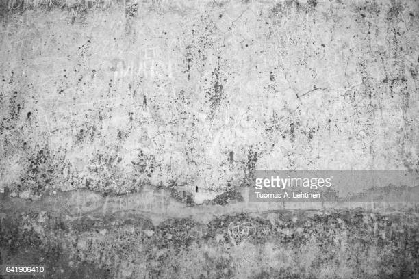 Weathered, aged and cracked gray stone wall with names scratched on it in black&white.