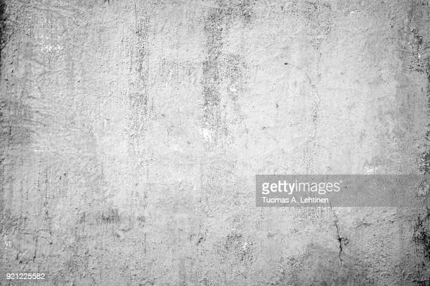 Weathered and dirty concrete wall texture background in black and white with vignetting