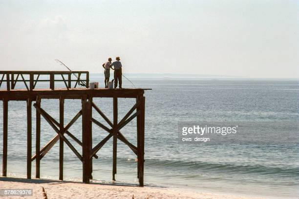 weathered and worn fishing pier with 2 fishermen juts into the gulf of mexico - gulf shores alabama stock pictures, royalty-free photos & images