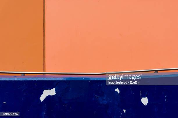 Weathered Blue Retaining Wall Against Orange Wall