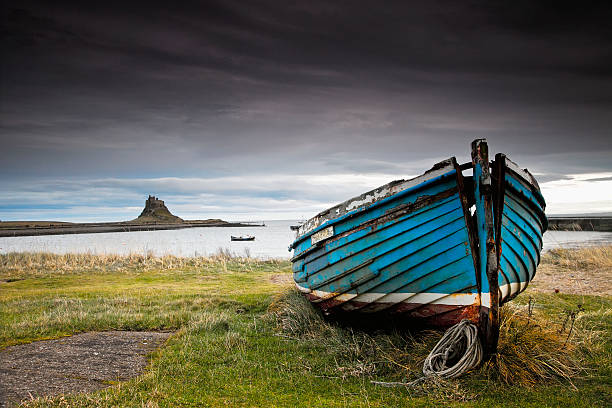 A Weathered Boat Sitting On The Shore With Lindisfarne Castle In The Distance