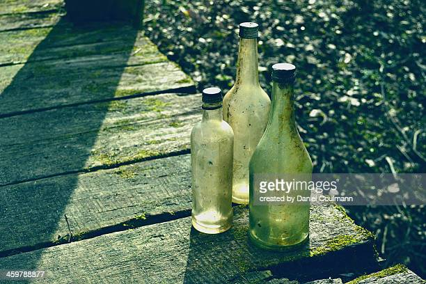 Weathered bottles on wooden plank