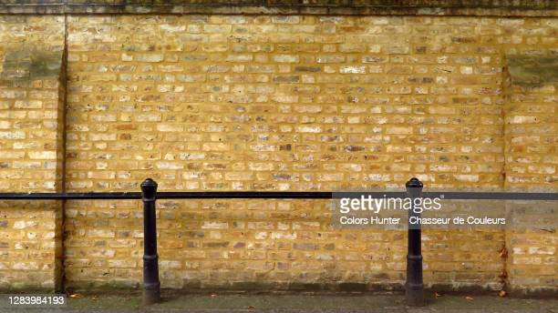 weathered brick wall with black metal grid in london - city life stock pictures, royalty-free photos & images