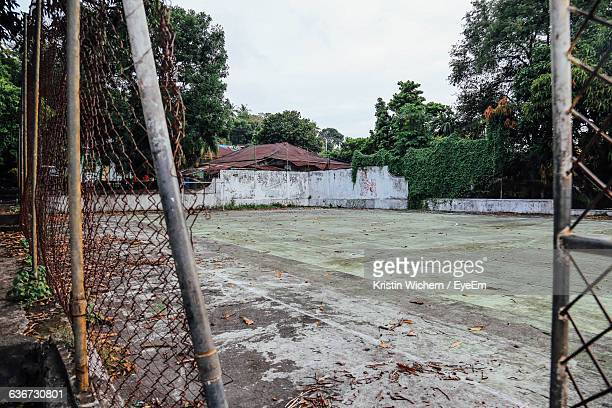 weathered chainlink fence against abandoned soccer field - abbandonato foto e immagini stock