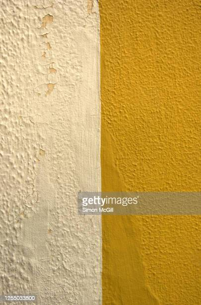 weathered concrete stucco building exterior painted half cream, half yellow - ツートンカラー ストックフォトと画像