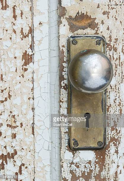 Weathered doorknob and painted door on garden shed, close-up