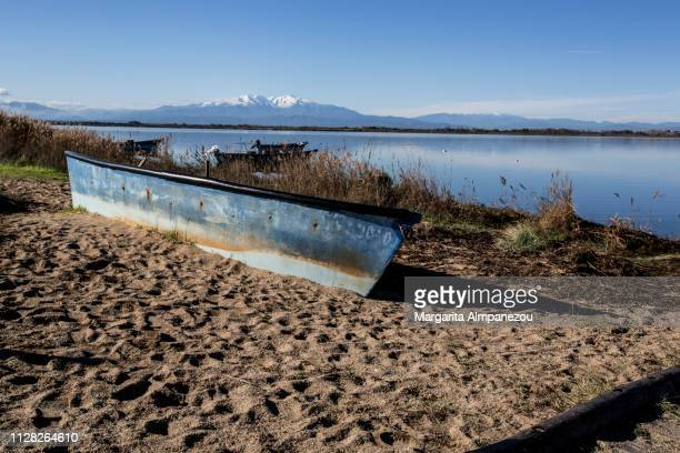 Weathered fishing boat on the sand next to a calm lake