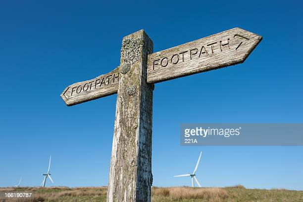 Weathered footpath sign and wind turbines
