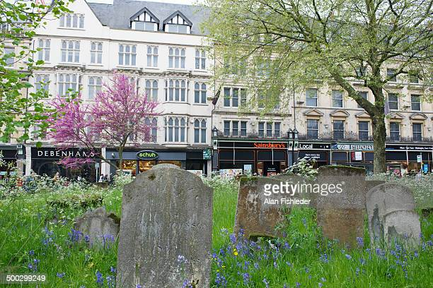 Weathered headstones in a historical cemetery contract with busy retail stores on Magdalen Street in downtown Oxford, England. The cemetery is...