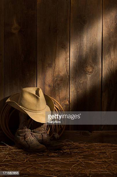 Weathered packer's boots,hat & rope on barn floor-sunbeam on barnwood wall
