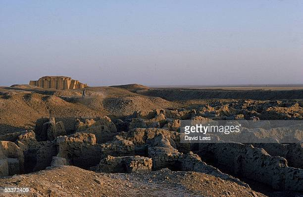 Weathered remains of a partially restored ziggurat dating from 2000 BC and the crumbling ruins of a city in the foreground at the site of the ancient...
