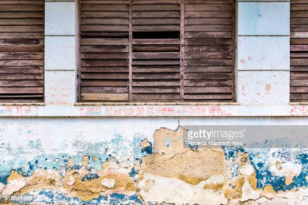 Weathered wall with wooden Miami windows on a primary school in the center part of the city