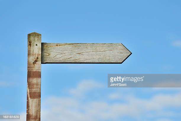 Weathered wooden sign post against blue sky