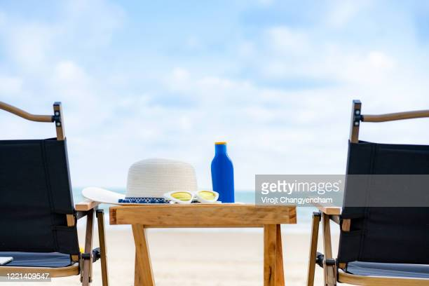 weave hat with sunglass and sunscreen bottle on the beach chair - uv protection stock pictures, royalty-free photos & images