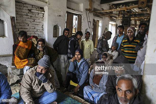 Weaver Mumtaz Ahmed front left sits with colleagues during interviews at a workshop in Varanasi Uttar Pradesh India on Thursday Dec 8 2016 Indian...