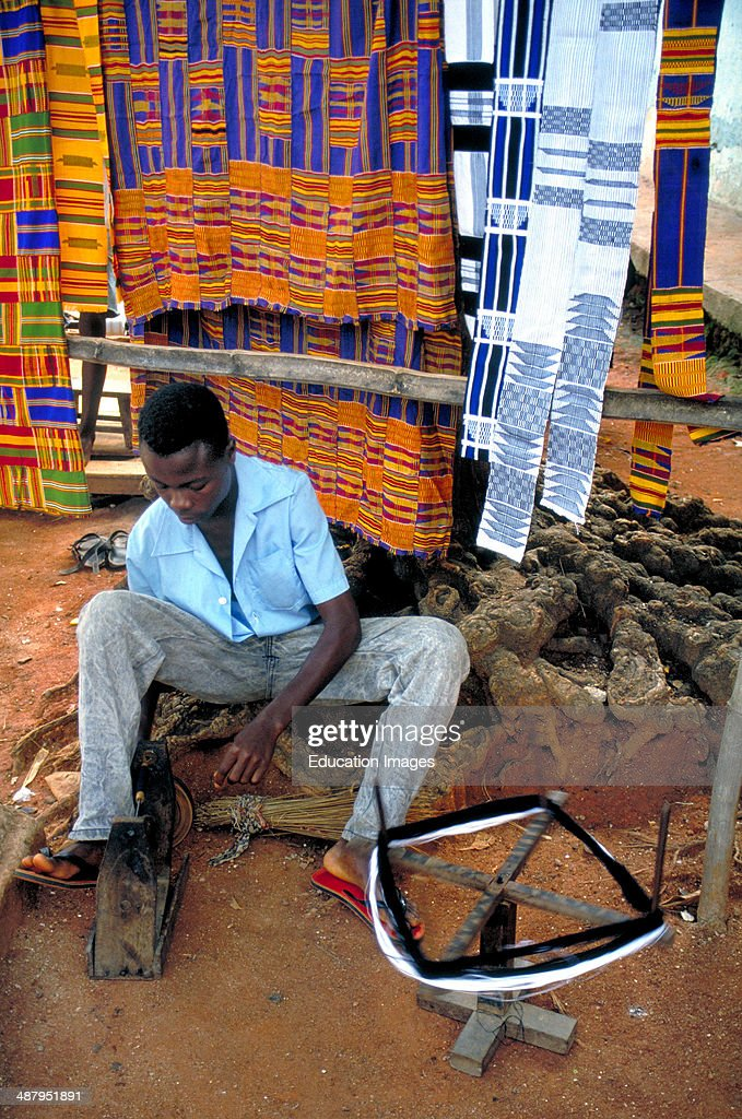 A weaver spins yarn and winds it onto bobbins to be used to make kente cloth : News Photo