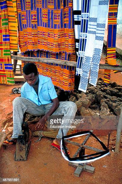 A weaver spins yarn and winds it onto bobbins to be used in a loom to make traditional kente cloth In the village of Bonwire in the Ashanti Region of...