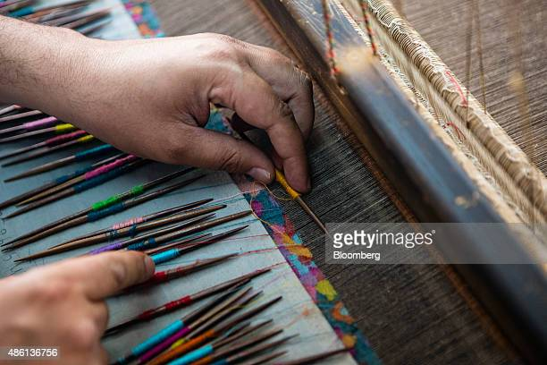 A weaver uses kani sticks weaving different colors of pashmina threads to make a kani shawl at a home workshop in Srinigar Jammu and Kashmir India on...