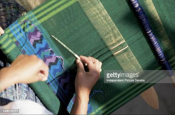 A Weaver working on a backstrap loom Guatemala