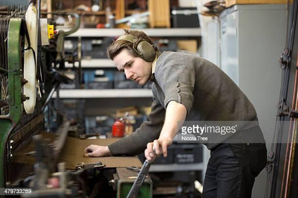 Weaver working on a power loom.