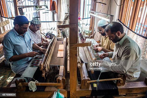 Weavers work pashmina on a handloom to make a kani shawl at a home workshop in Srinigar Jammu and Kashmir India on Monday Aug 24 2015 Pashmina goats...