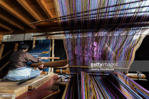 Weavers working on traditional looms in studio