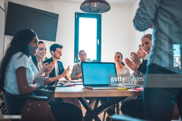 Web designers applauding in board room