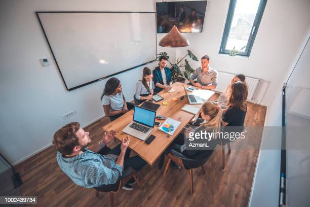 Web designers discussing in board room