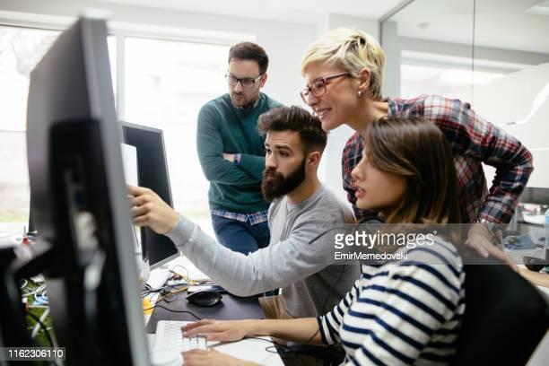 一緒にプロジェクトでオフィスで働くwebデザイナー - デザインスタジオ ストックフォトと画像