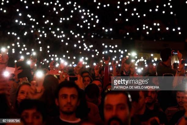 Web Summit's attendees light up the flash lights of their phones at the main stage during the Web Summit at Parque das Nacoes in Lisbon on November 9...